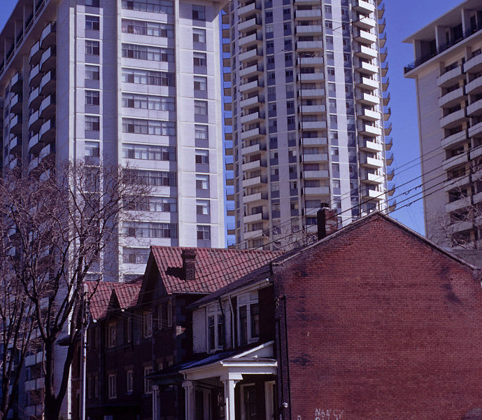 Figure 3. View of Village Green apartment tower complex behind razed lot and older housing stock, facing east on Maitland Street, between Church and Yonge Streets, Wednesday, 31 March 1971. [City of Toronto Archives: item 69, file 61, fonds 1526 (Harvey R. Naylor Fonds)].