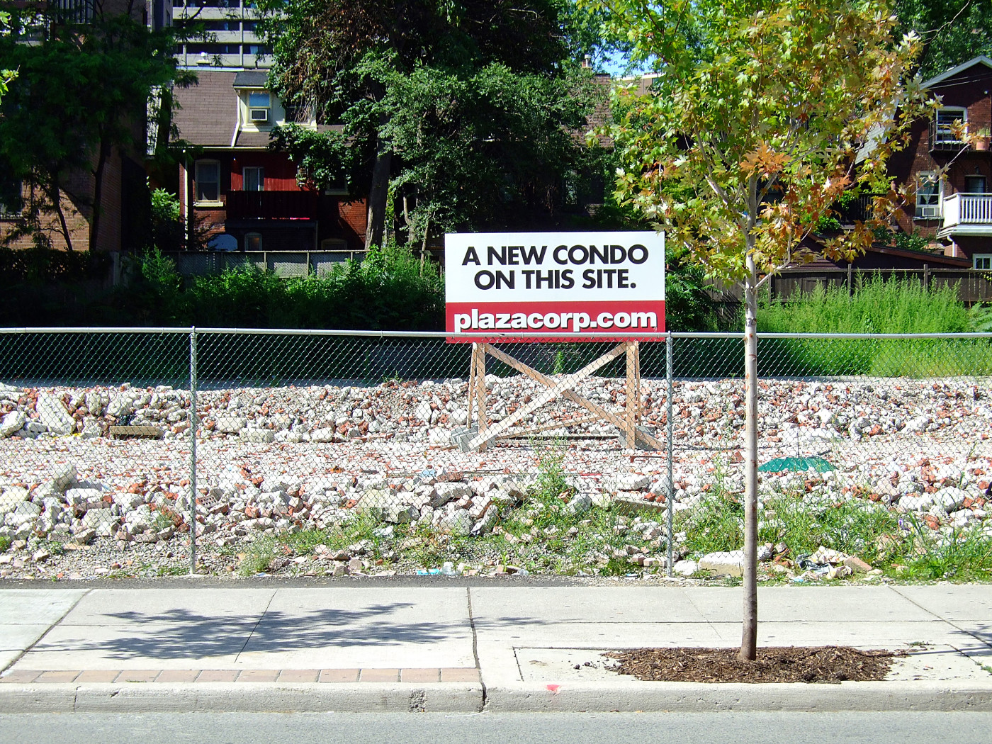 "Figure 10. Pending condo development at 50 Wellesley Street East, August 2008, with visible remnants of a just-demolished, four-storey brick office building. As of 2015, this development is not yet built. Branded both as ""Plaza"" and ""50 Wellesley East"", its developers still have a positive opportunity to inscribe the ""Plaza"" (or ""Plaza at 50 Wellesley"") name permanently to the tower and to enhance legibility of the streetscape along Wellesley. Owing to its extended presence for at least four seven years, the ""Plaza"" name serves already as an effective, if ephemeral, toponym. [Idlewild]"