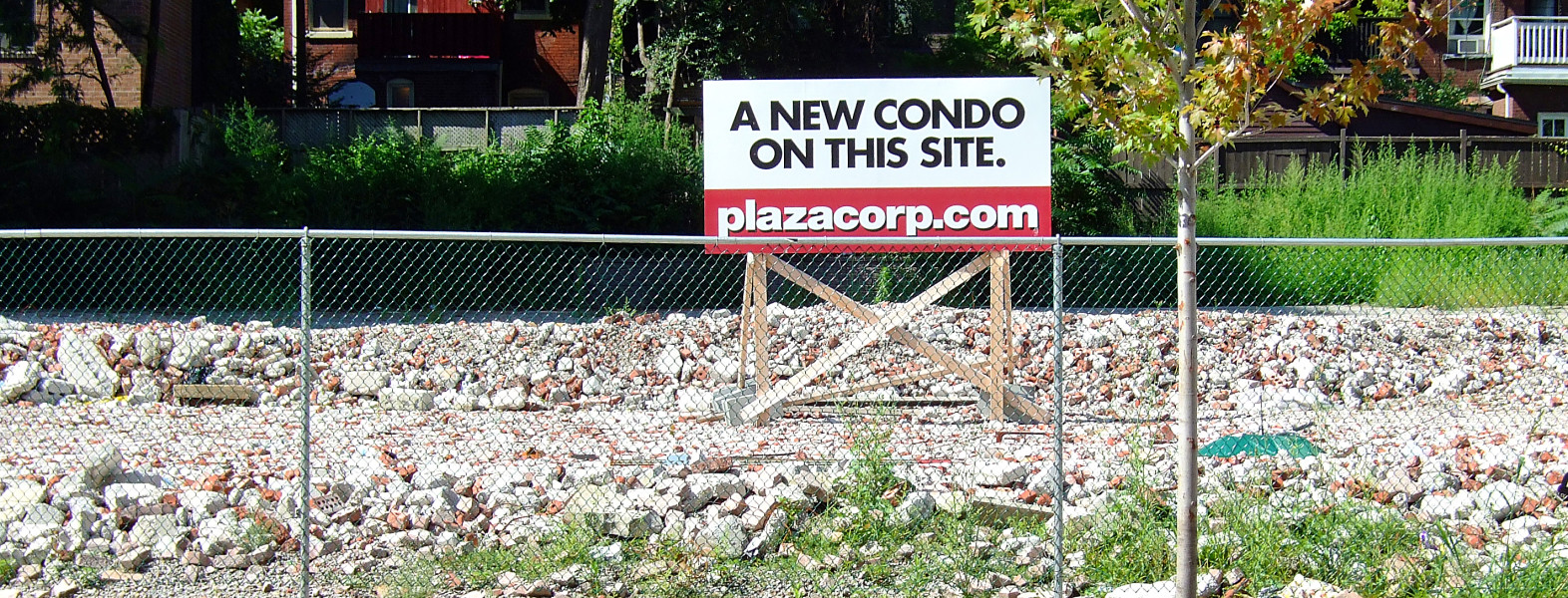 "Figure 10. Pending condo development at 50 Wellesley Street East, August 2008, with visible remnants of a just-demolished, four-storey brick office building. As of 2012 2015, this development is not yet built. Branded both as ""Plaza"" and ""50 Wellesley East"", its developers still have a positive opportunity to inscribe the ""Plaza"" (or ""Plaza at 50 Wellesley"") name permanently to the tower and to enhance legibility of the streetscape along Wellesley. Owing to its extended presence for at least four seven years, the ""Plaza"" name serves already as an effective, if ephemeral, toponym. [Idlewild]"