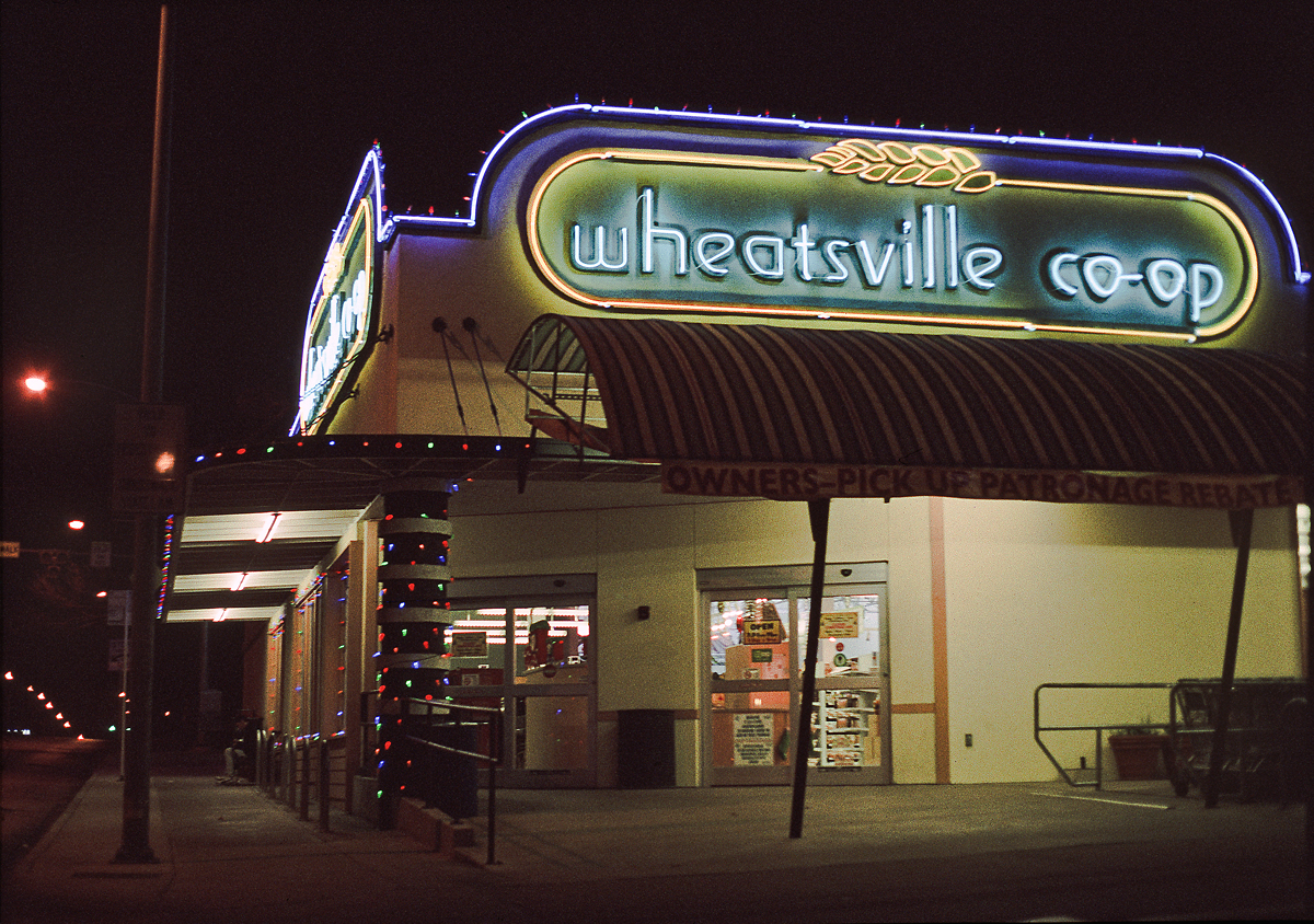 """""""Sitting Alone"""". Wheatsville Co-operative Grocery. Excellent, decades-old neon wayfinding fixture of northern Guadalupe Street. Monday, 20 December 2010. [Idlewild]"""