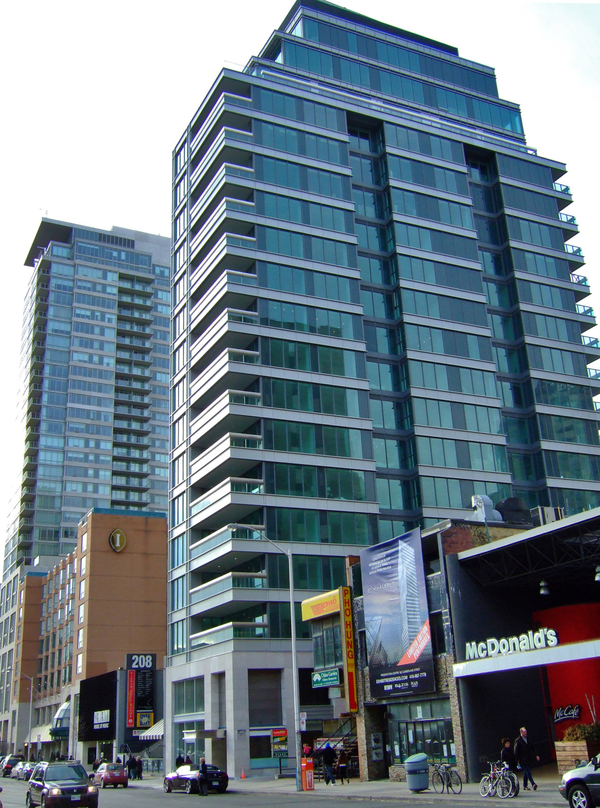 """Figure 3. Street view of Museumhouse nearby another new condo tower, One Bedford at Bloor (background), 2012. The Intercontinental Hotel, the brick-clad, mid-rise edifice, was prior to 2010 the tallest building along this corridor (and the only with permanent inscriptions). It is adorned with an """"I"""" brand mark. To describe One Bedford at Bloor and Museumhouse is challenging: they typify the built form of Toronto's new condo towers. [Idlewild]"""