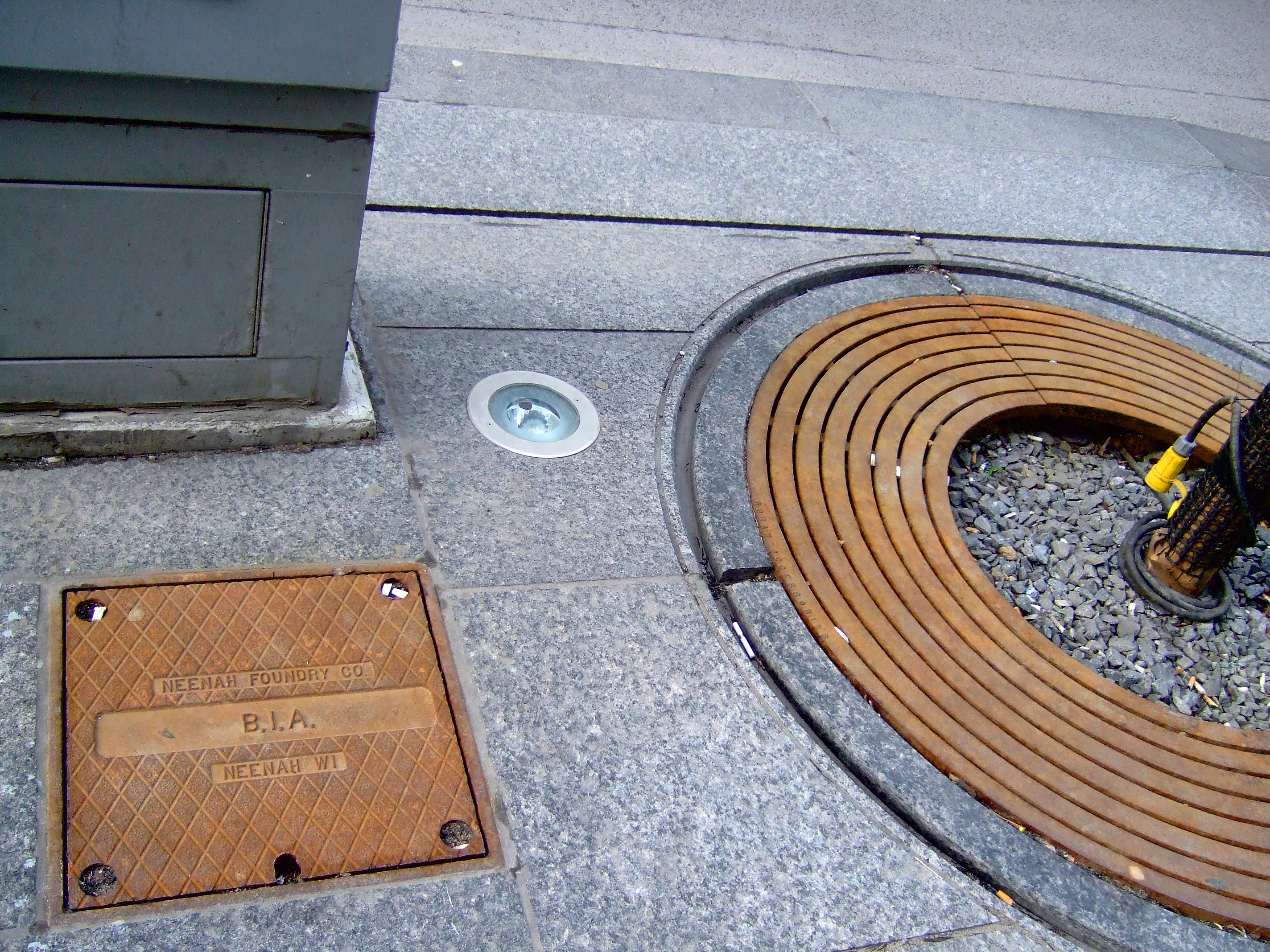 """Figure 7. BIA streetscape treatments to public sidewalks within the Bloor-Yorkville BIA zone. Street furniture """"props"""" are funded by compulsory dues received from BIA members annually — a private levy tool legalized by the province in 1970, giving rise to the Canadian BIA model. Props for public spaces in Bloor-Yorkville BIA feature granite-slabbed sidewalks, sunken pot lights for new trees, and stone """"benches"""" engineered to minimize lounging or resting time (or accommodation for denizens with disabilities). This bench design (not shown) deprives the public realm of the means to accommodate denizens with reasonably comfortable seating; rather, the design coaxes denizens to minimize their sitting presence and seek out private sites of consumption which promise not only the illusion of public spacing (e.g., a sidewalk café), but also have cosier seating configurations. Within the Bloor-Yorkville BIA, City of Toronto street furniture is missing — including the absence of ubiquitous city bike ring posts designed to secure two bikes, replaced by BIA-approved bike lock """"columns"""" (which have difficulty accommodating more than one bike and are incompatible with several popular bike-locking solutions). [Idlewild]"""