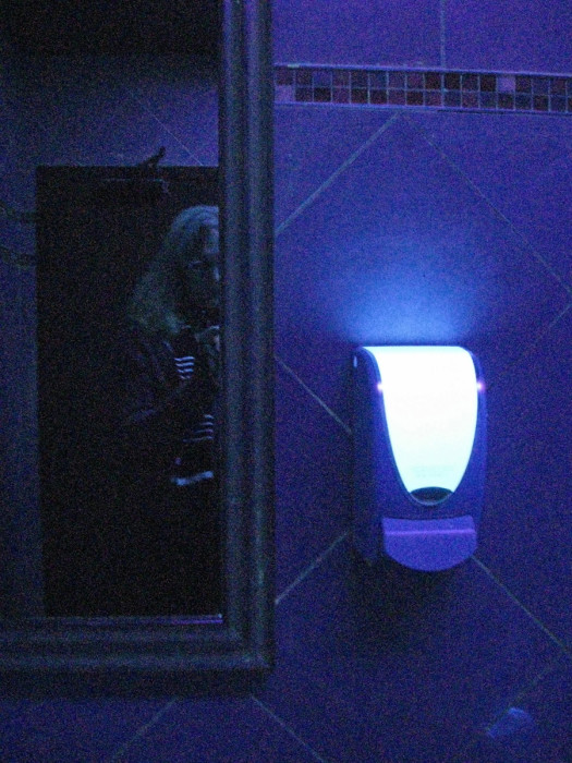 Figure 14. The qualitative impact of fluorescent UV black lights inside a restaurant washroom in lieu of conventional fluorescent lights: inside a McDonald's in Montréal's gay village, 2011. UV lighting, implemented in this way, makes it tougher (but not impossible) to locate a vein for intravenous drug injection. UV black lighting also makes everything prohibitively difficult to see with the human eye. (The bright object, centre right, is not a light source, but a reflective fluorescing surface.) [Idlewild]